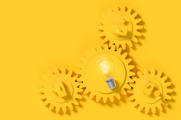 Work desk and light bulb yellow color on the gear with copy space for your text.
