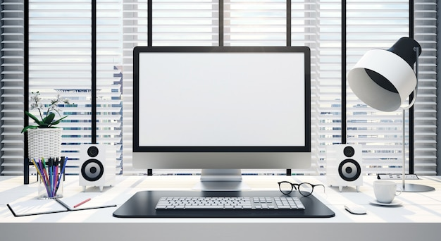 Work desk with blank computer screen in an office