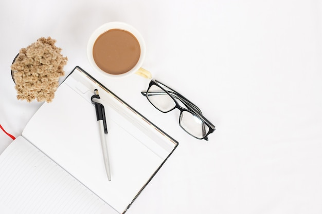 Work desk with cup of coffee and notes isolated on white background