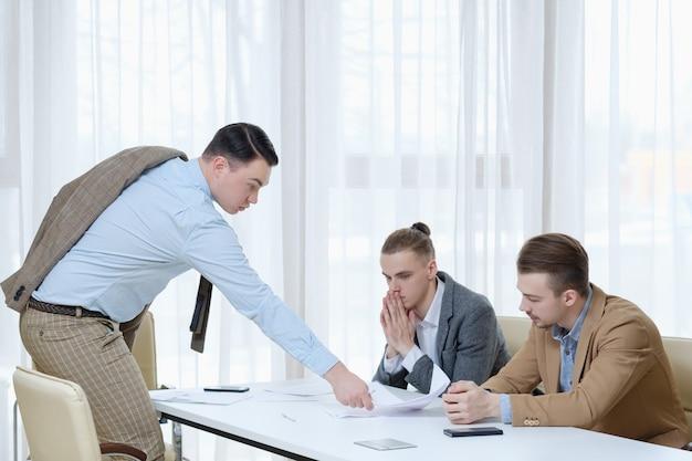 解雇と自発的解雇。滞納した従業員に辞表に署名することを申し出ている上司。