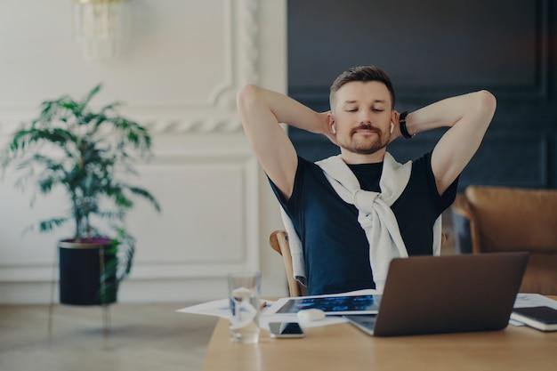 Работа выполнена. расслабленный человек-фрилансер или предприниматель в беспроводных наушниках сидит за столом с руками за головой, смотрит бизнес-вебинар или слушает оратора на ноутбуке, работая удаленно из дома