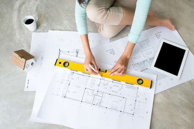 Work everywhere. confident young beautiful asian woman working with  blueprint while sitting on the floor at home