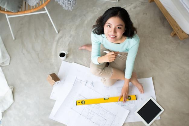 어디서나 일하세요. 집 바닥에 앉아 있는 동안 청사진 작업을 하는 자신감 있는 젊은 아름다운 아시아 여성