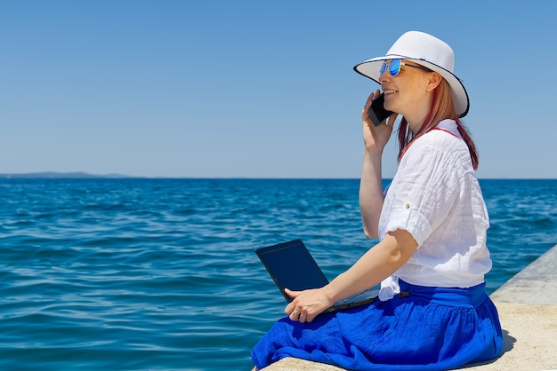 麦わら帽子をかぶった若い女性の女性フリーランサーがノートパソコンで作業しているときに、どこからでも作業できます。