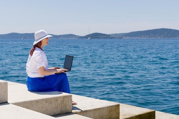Работа отовсюду, вид сбоку молодой женщины-фрилансера в соломенной шляпе, работающей на ноутбуке, пока с ...