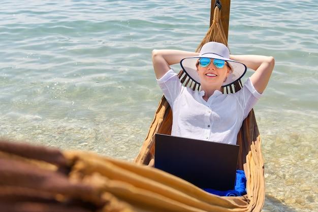 해변에서 노트북 작업을 하는 밀짚 모자를 쓰고 웃는 젊은 여성 프리랜서