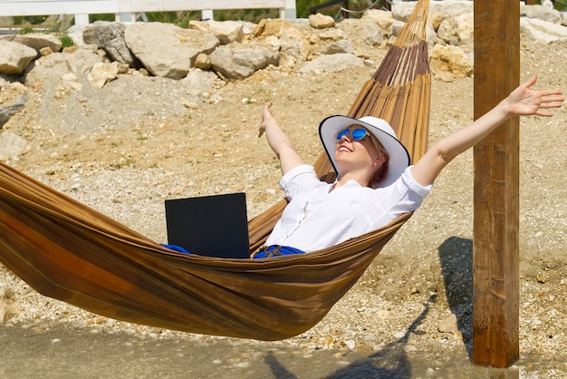 Work from anywhere young smilyng woman female freelancer in straw hat working on laptop on beach