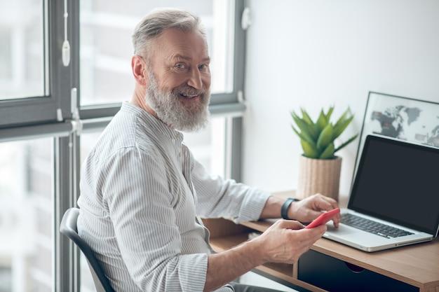 在宅勤務。自宅で働く手にスマートフォンを持つ白いtシャツの男