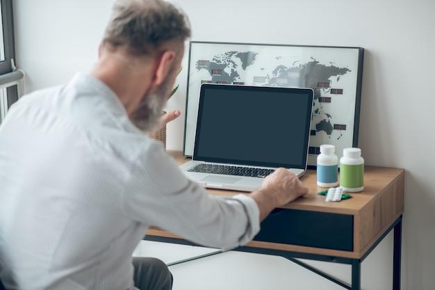 在宅勤務。テーブルに座ってテーブルで働いている男
