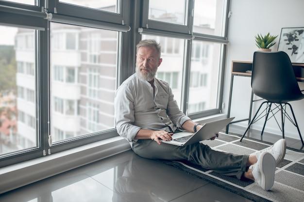 在宅勤務。床に座ってラップトップで作業しているラップトップを持つ男