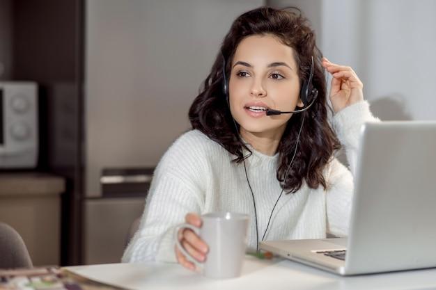 집에서 일하십시오. 집에서 일하는 동안 노트북에 앉아 이어폰에 여자