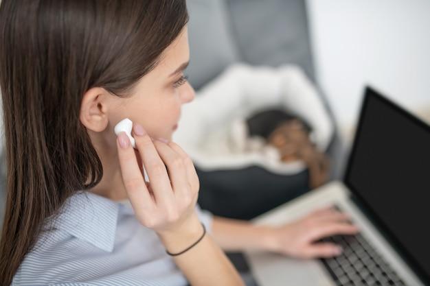 在宅勤務。ソファに座ってノートパソコンで作業している女性