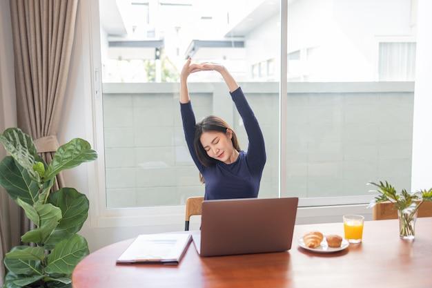 在宅勤務のコンセプトで、自宅で離れた場所で仕事をしながらリラックスしている女性起業家が腕を伸ばしています。
