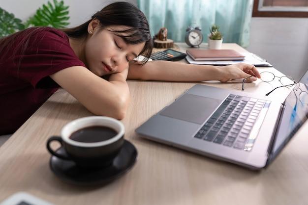 집에서 일하는 여성 프리랜서는 사무실에서 긴 검은색 컵 근처에서 일하는 동안 피곤하고 잠을 자고 있습니다.