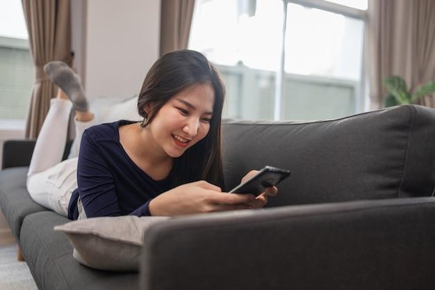 在宅勤務のコンセプトインターネットサーフィンをしているリビングルームの灰色のソファに横たわっている若い女性。