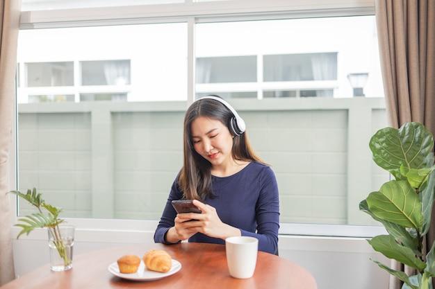 自宅のコンセプトから仕事をするヘッドフォンを身に着けている若い女性が、デザートとテーブルの上で飲み物を飲みながらお気に入りのプレイリストを聴いている瞬間を楽しんでいます。