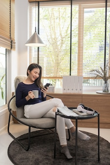 Work from home concept a confident woman sitting on a modern chair hold a cup of coffee and another hand typing a keyboard on her smart phone.