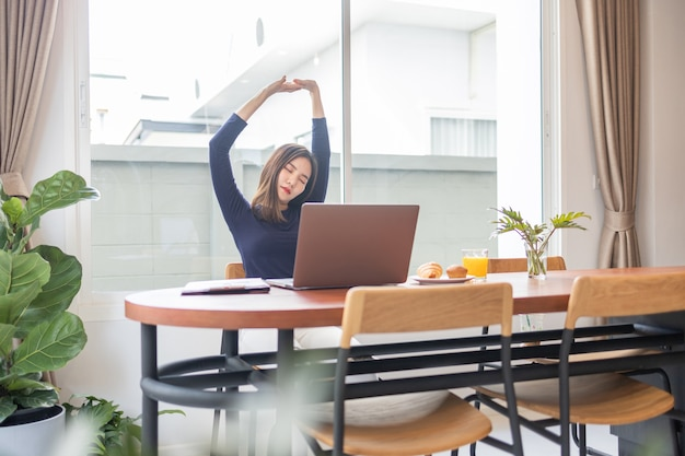 Work from home concept a female entrepreneur being relaxed stretching her arms while working remotely in her house.