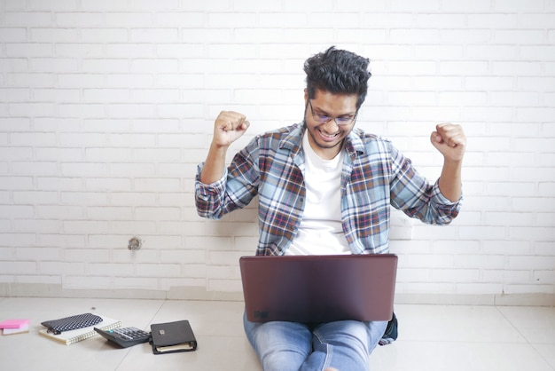 自宅のコンセプトから仕事ラップトップで作業床に座って幸せな若い男