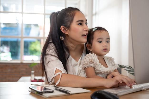 ホームコンセプトから動作します。母と娘の母が在宅勤務中にコンピューターとインターネットを使用して