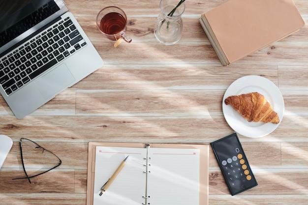 Работа из дома концепции. открытый планировщик, ноутбук, смартфон и чашка чая со свежим круассаном, вид сверху