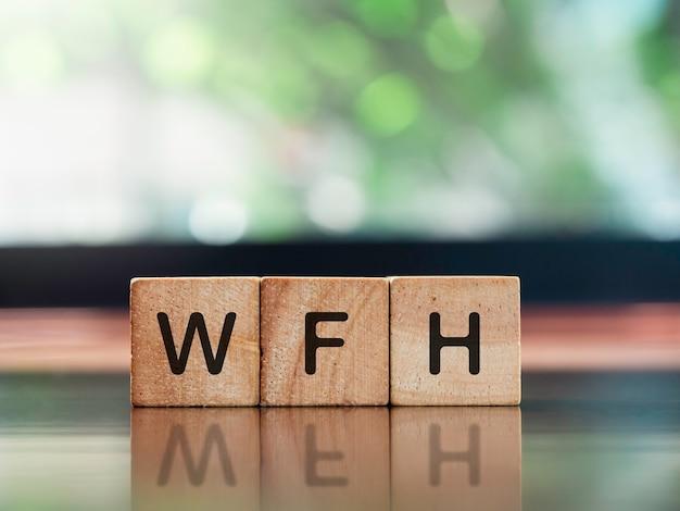 재택 개념에서 작동합니다. wfh, 갈색 나무 책상에 있는 나무 큐브 블록에 있는 단어와 복사 공간이 있는 녹색 자연 배경.