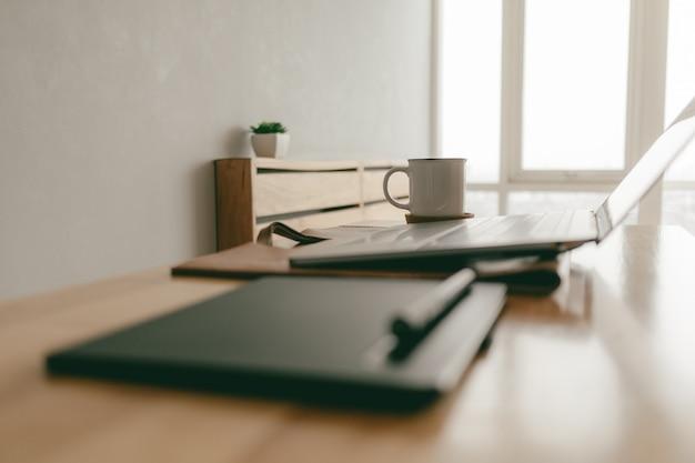 Работа из дома креативных предметов, набор из ноутбука и ручки планшета в квартире.