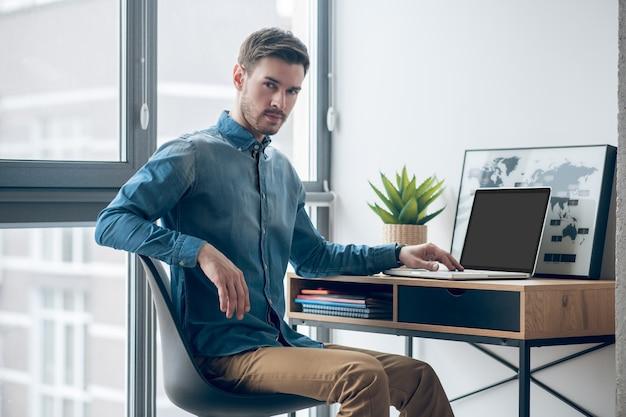 집에서 일하십시오. 검은 머리 남자 테이블에 앉아 노트북에서 작업