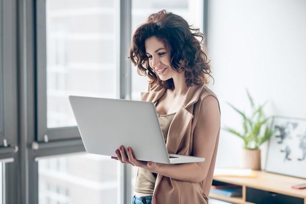 집에서 일하십시오. 노트북에서 작업하고 집중 찾고 검은 머리 예쁜 여자