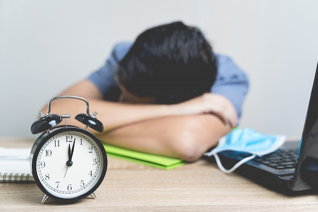 Работа из дома во время вспышки вируса. будильник на таблице в полночь с нерезкостью бизнесмен работает от дома и он спит из-за усталости на таблице, концепции дела.