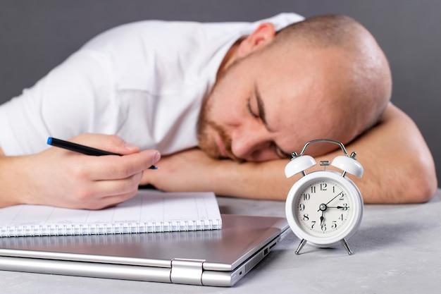 바이러스가 발생하는 동안 집에서 일하십시오. 테이블에 알람 시계, 남자는 집에서 일