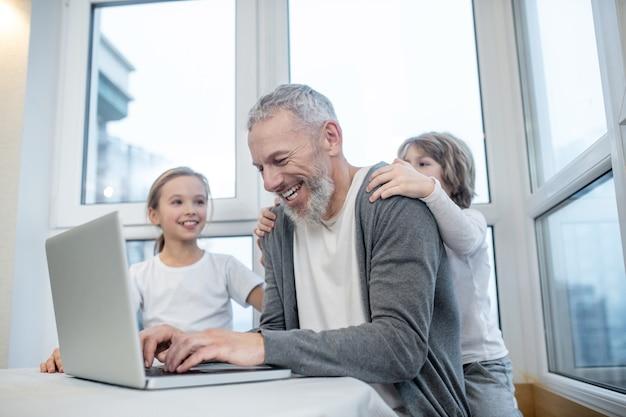 在宅勤務。彼の子供たちが彼を妨害している間、ラップトップで作業している白髪のひげを生やした男