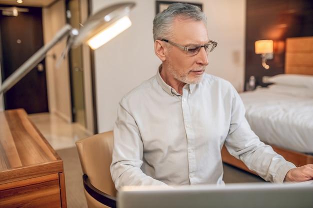 在宅勤務。ノートパソコンで作業し、真剣に見える眼鏡の白髪の男