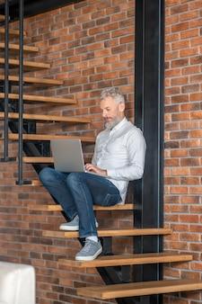 집에서 일하세요. 노트북으로 계단에 앉아 있는 회색 머리 남자