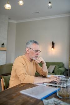 Работа из дома. седовласый мужчина работает на ноутбуке и выглядит занятым