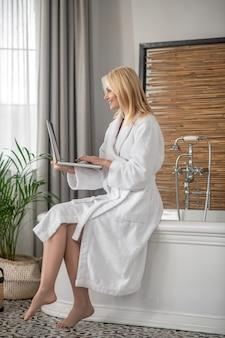 在宅勤務。自宅からラップトップで働く長髪のブロンドの女性