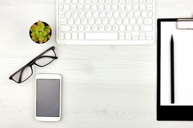 在宅勤務。白いキーボード、老眼鏡、ペット、ノートブックのあるオフィスフラットレイ