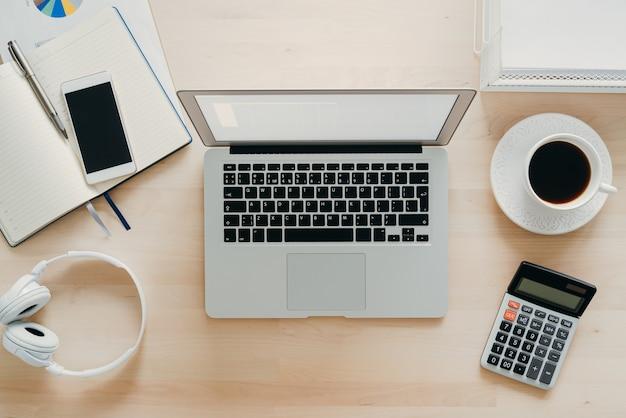 在宅勤務、オンライン学習。木製の机、テーブルの上のラップトップ。上面図。遠隔教育。フリーランサー、デジタル遊牧民の概念
