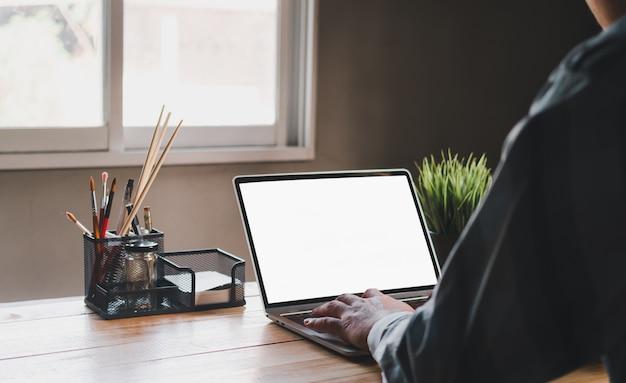 自宅またはホームオフィスで作業します。白い画面のノートパソコンで作業する男性