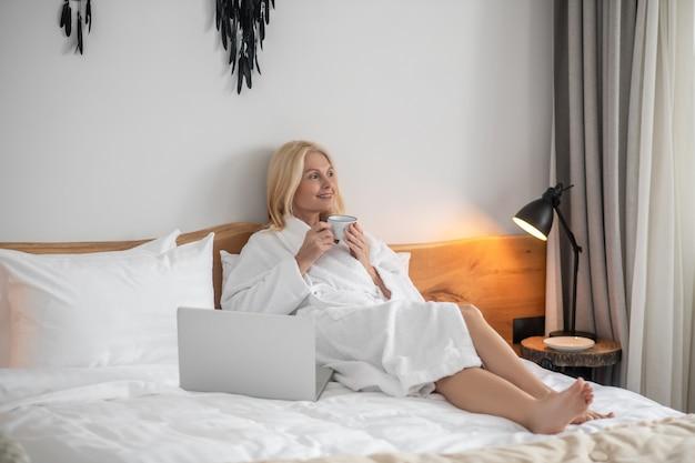Работа из дома. довольно блондинка работает дома и чувствует себя комфортно