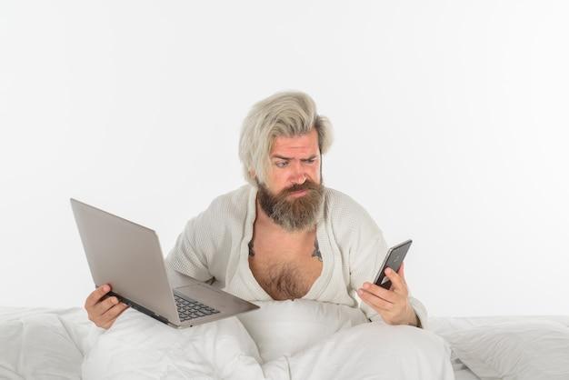 Работа на дому, самоизоляция, человек, работающий в постели, сбивает с толку человек в постели, работающий с ноутбуком и