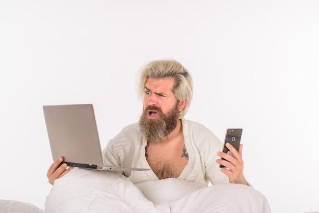 Работа на дому, самоизоляция, человек, работающий в постели, сбивает с толку мужчина в постели, работая с ноутбуком утром