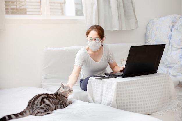 가정, 공부, 창작 공간, 개념에서 일하십시오. 노트북 및 컴퓨터 집에서 작업하는 도우미 고양이 함께 비즈니스 아시아 여자 프리랜서. 바이러스 발발 covid-19에 격리 된 집에있는 사람들