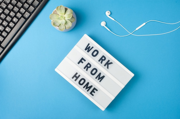 在宅勤務-青い背景の職場のディスプレイライトボックスのテキスト。黒のキーボードと白のイヤホン。フリーランスの仕事のコンセプト