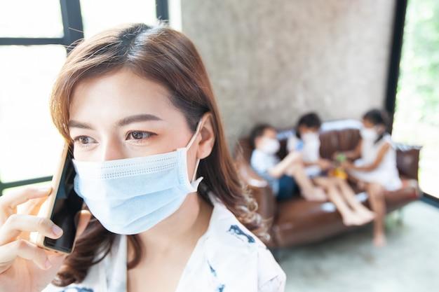 코로나 바이러스 covid-19에 대한 격리 검역소에있는 여성 covid-19는 전화로 얘기하고 집에서 일하는 동안 보호 마스크를 쓰고 코로나 바이러스가 발생하는 동안 집에서 놀고 있습니다.