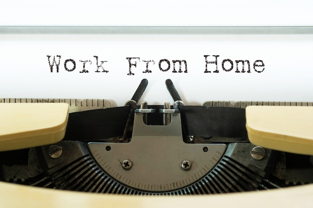Work from home word typed on a yellow vintage typewriter.