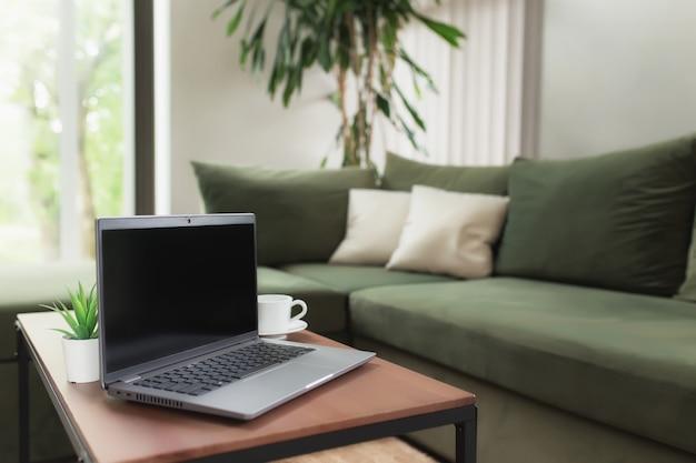 Работа из дома, рабочее место, рабочий стол, концепция удаленной работы, серый тонкий портативный компьютер черный пустой экран на коричневый деревянный стол с белой чашкой кофе, зеленый диван, цветочный горшок. стильные апартаменты