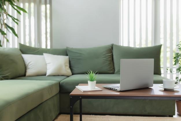 집, 작업 공간, 데스크탑, 원격 작업 개념, 갈색 나무 테이블에 있는 회색 얇은 노트북 컴퓨터, 흰색 커피 한 잔, 녹색 소파, 화분, 메모장이 있습니다. 세련된 아파트 컴포트 존