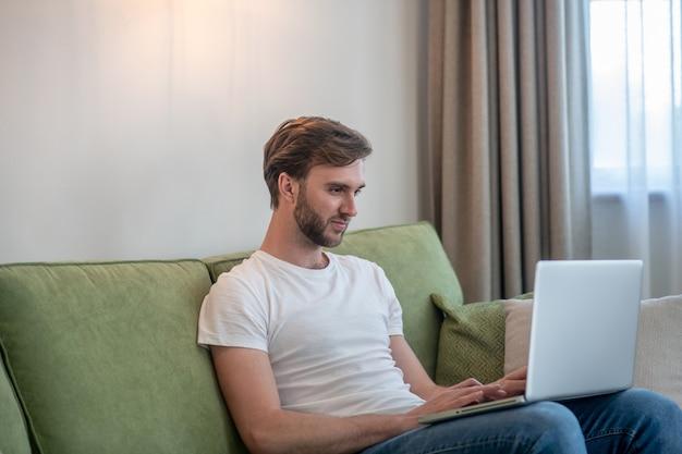 Работа из дома. молодой бородатый человек, работающий на ноутбуке и выглядящий вовлеченным