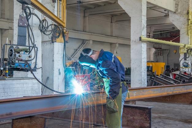 Рабочий газосварочный аппарат режет швеллер